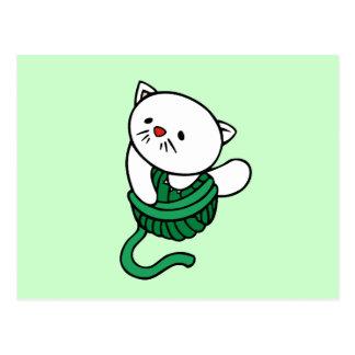 Gatito blanco con las camisetas y los regalos del postal