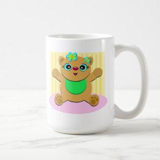 Gatito del bebé con las flores verdes del babero y taza clásica