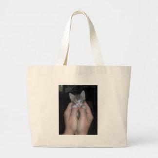 Gatito en manos bolsas de mano
