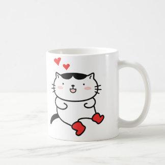 Gatito en tazas de café de las botas