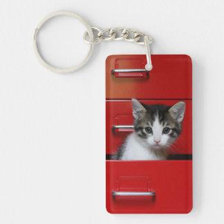 Gatito en un cajón rojo llavero rectangular acrílico a doble cara