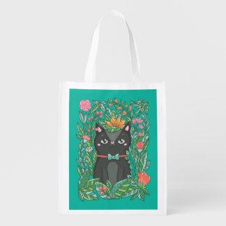 Gatito negro en el fondo de la turquesa del jardín bolsa de la compra