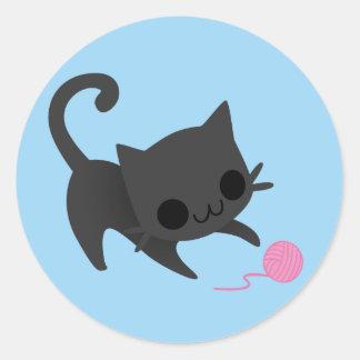Gatito negro lindo que juega con una bola del pegatina redonda