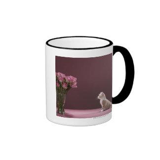 Gatito que mira el florero de rosas taza de café