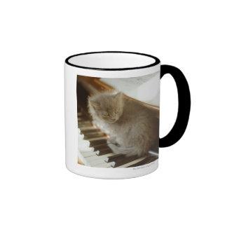 Gatito que se sienta en el teclado de piano, taza de dos colores