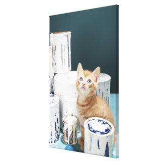 Gatito que se sienta entre las latas de la pintura impresión en lona