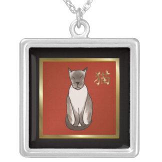 Gatito siamés con rojo y el collar del oro
