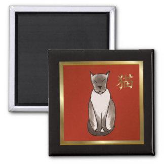 Gatito siamés con rojo y el imán del oro