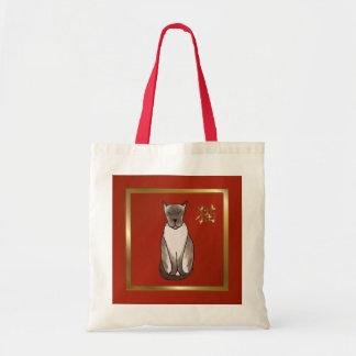 Gatito siamés con rojo y la bolsa de asas del oro