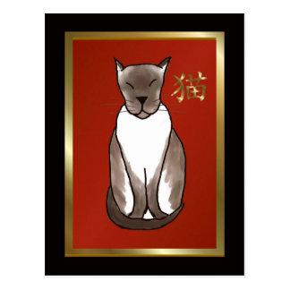 Gatito siamés con rojo y la postal del oro