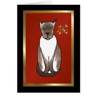 Gatito siamés con rojo y la tarjeta de nota de oro