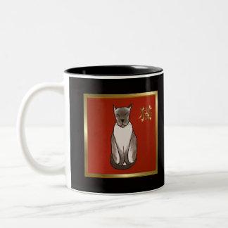 Gatito siamés con rojo y la taza del oro