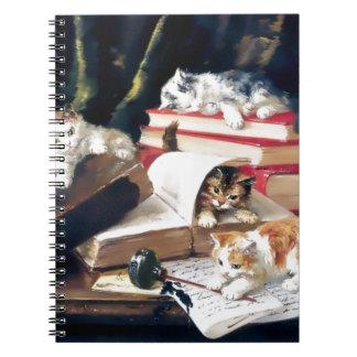 Gatitos que juegan en un escritorio cuaderno