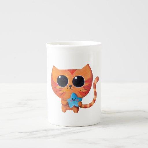 Gato anaranjado lindo con la estrella taza de porcelana