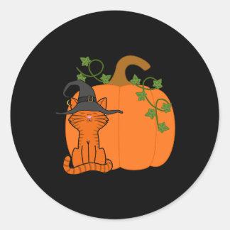 Gato anaranjado que se sienta con la calabaza de pegatina redonda