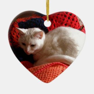 gato blanco en la manta roja del punto del ganchil ornamento de reyes magos