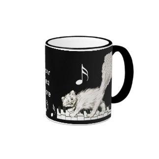 Gato blanco en llaves del piano tazas de café