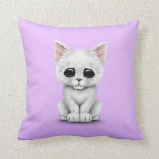 Gato blanco lindo triste del gatito en púrpura cojín