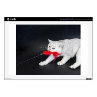 Gato blanco que juega tirando del juguete rojo portátil 43,2cm skin