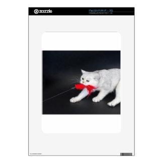Gato blanco que juega tirando del juguete rojo skins para iPad