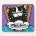 Gato caprichoso lindo del smoking que come la sopa tapete de ratón