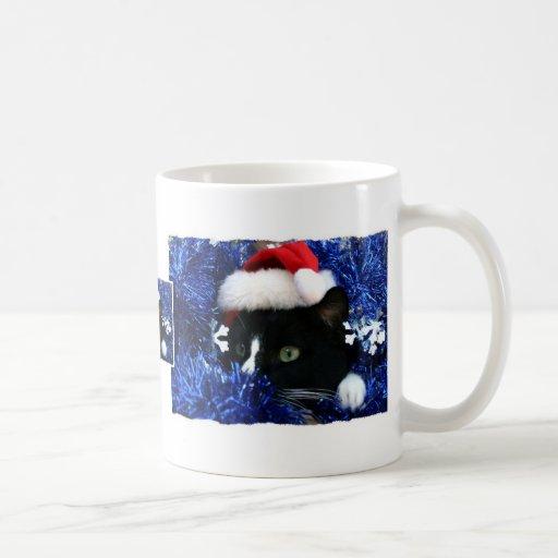 Gato con el gorra de santa que mira hacia fuera de tazas de café
