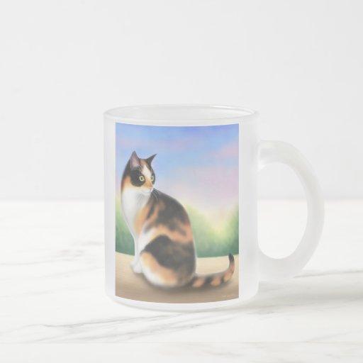 Gato de calicó en la taza de café de la puesta del
