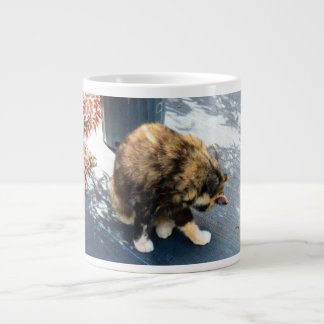 gato de calicó que lame las piernas traseras taza de café grande