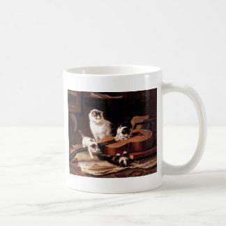 Gato de los gatitos que juega con lindo travieso d taza