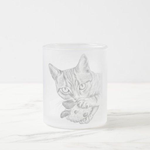 gato de tabby con la taza del vidrio esmerilado de