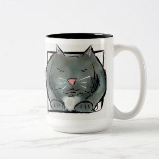 Gato del NQ en una taza de la caja