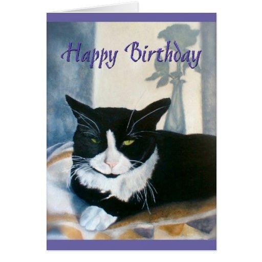 Gato del smoking del feliz cumpleaños al lado de tarjeta de felicitación