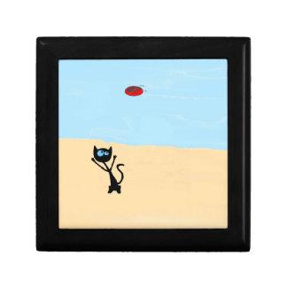 Gato en la playa que salta para el juguete del dis caja de regalo