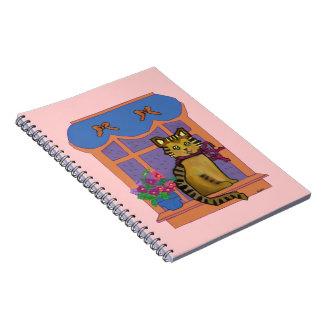 Gato en los cuadernos espirales de un Windowsill