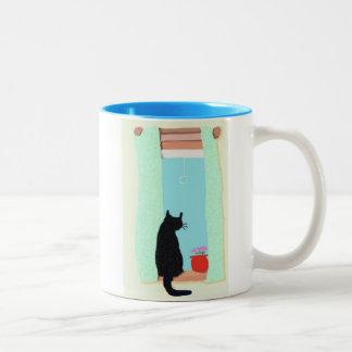 Gato en travesaño de la ventana taza