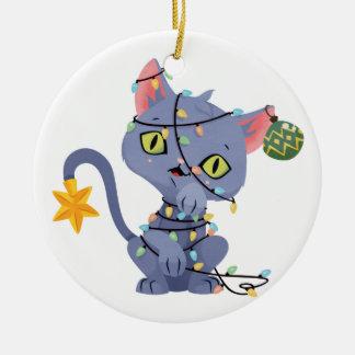 Gato enredado en el ornamento de las luces de adorno de navidad