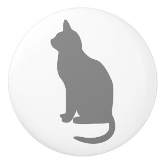 Gato gris que se sienta que hace frente a la pomo de cerámica