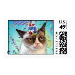 Gato gruñón en un gorra del cumpleaños sellos