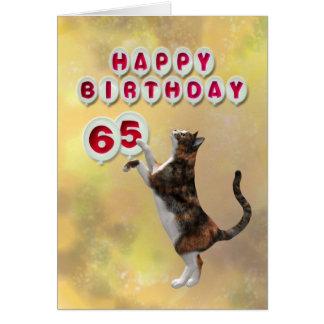 Gato juguetón y 65.os globos del feliz cumpleaños tarjeta de felicitación