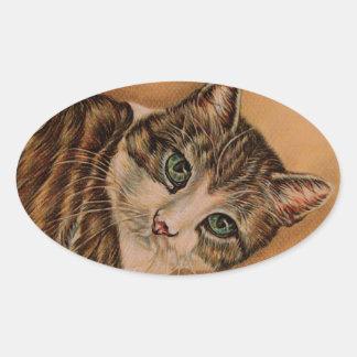 Gato lindo con los ojos verdes y la cabeza pegatina ovalada