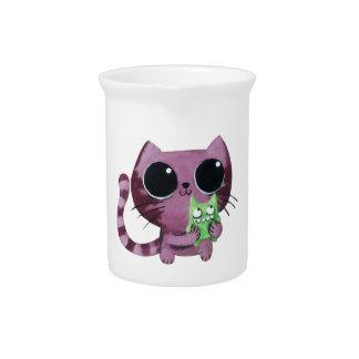 Gato lindo del gatito con el pequeño monstruo verd jarra de beber
