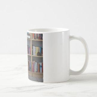 Gato lindo que duerme en los libros de la bibliote tazas