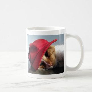 Gato lindo que lleva la taza roja del casquillo