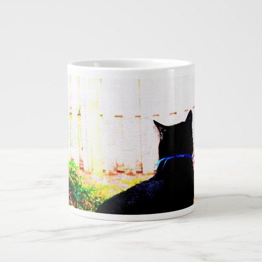 Gato negro de la parte posterior que mira hacia taza grande