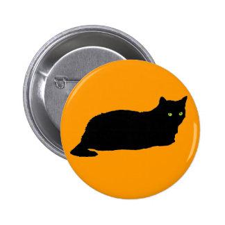 Gato negro de reclinación en el naranja pin redondo de 2 pulgadas