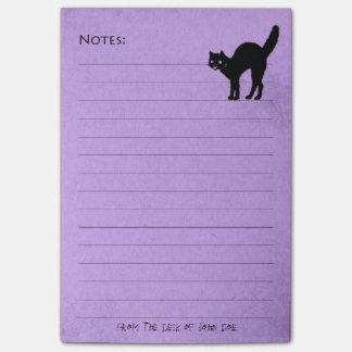 Gato negro en el cuaderno de notas púrpura de enca post-it notas