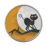 Gato negro en rama de árbol muerta latas de caramelos
