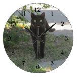 Gato negro en un jardín reloj redondo grande