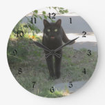 Gato negro en un jardín relojes de pared