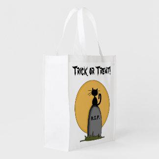 Gato negro en una lápida mortuoria bolsas para la compra